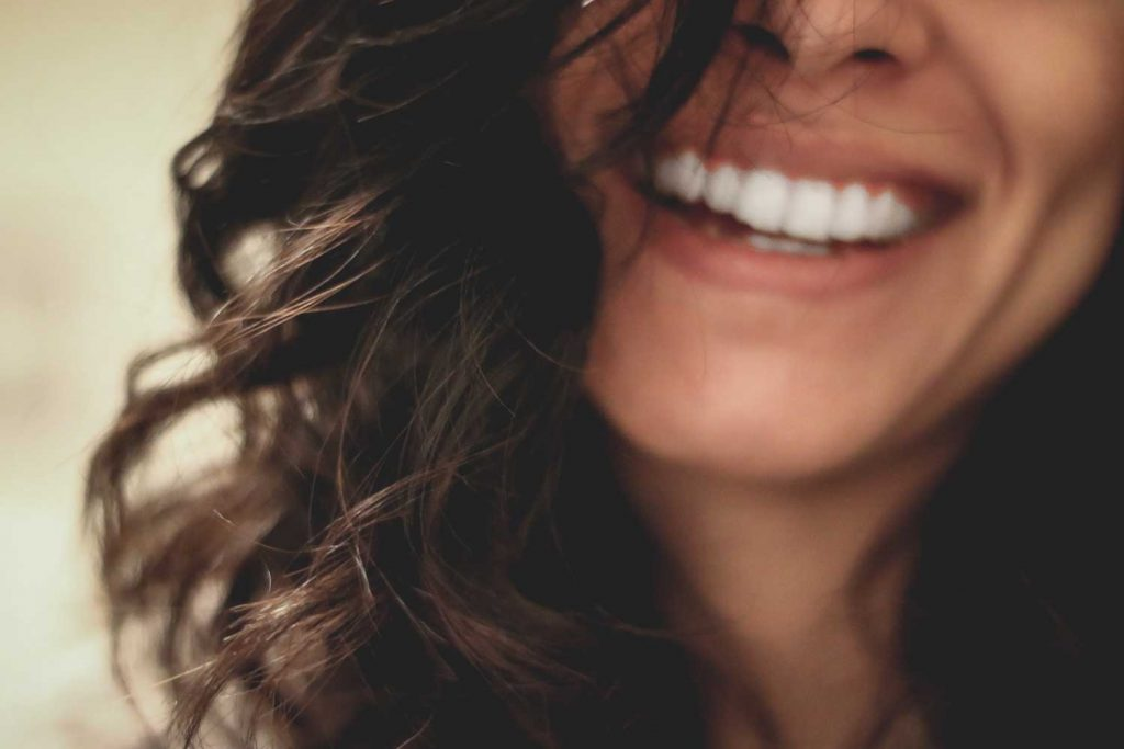 [A light skinned woman smiles broadly. You can only see her face from the nose to her neck. She has brown wavy hair.]