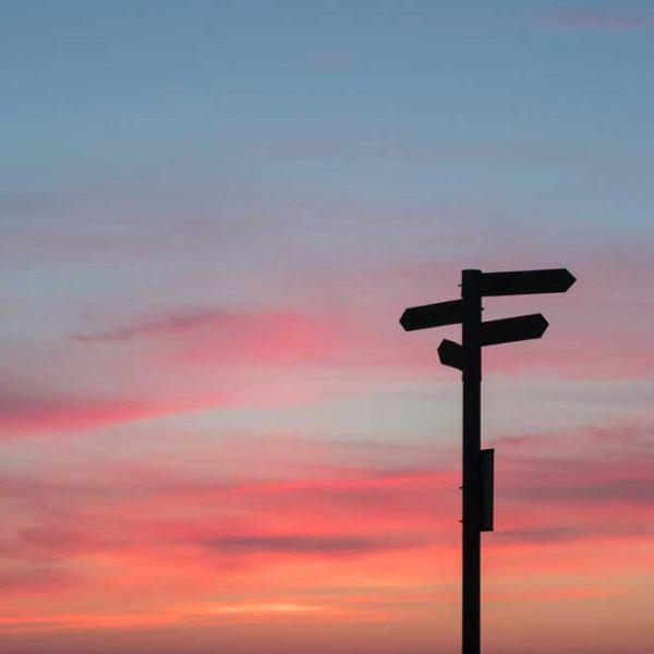 A silhouette of directionals on a post is backlit by a sunset with orange, red, pink, and blue colors.