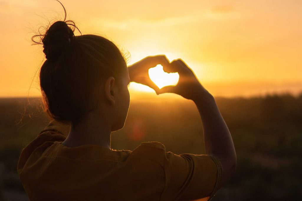 [A girl in a mustard yellow blouse has her hands in a shape of a heart. The sun is shining through the heart from a distance.]