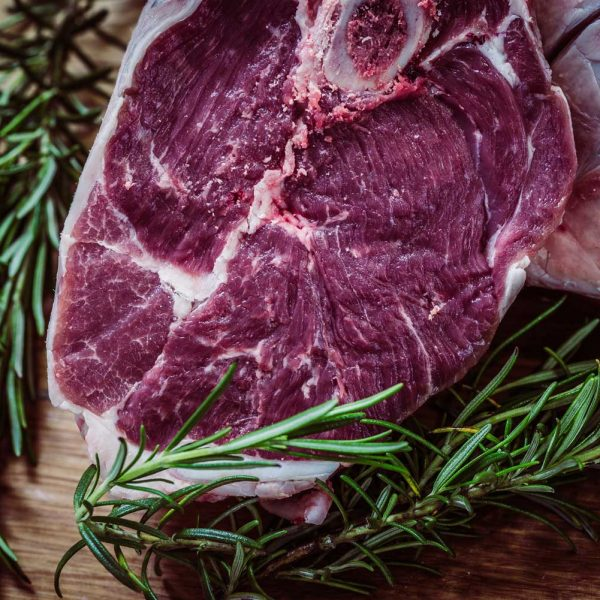 [A slab of butchered meat lays on a cutting board, surrounded by fat and fresh rosemary.]