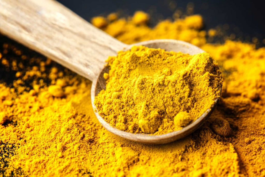 [A light colored wooden spoon has bright gold turmeric in it as well as underneath on a black background.]
