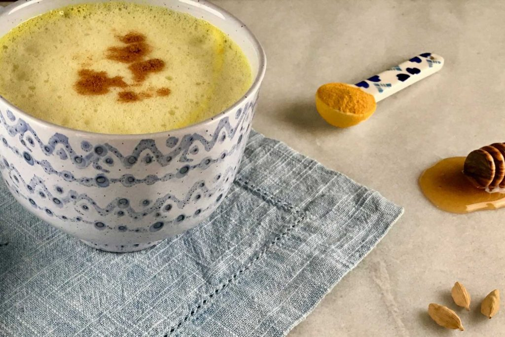 [A white and blue mug has a yellow color tea inside. Underneath the mug is a blue fabric placemat. Next to it is a spoon of turmeric, a stick of honey, and cardamon.]