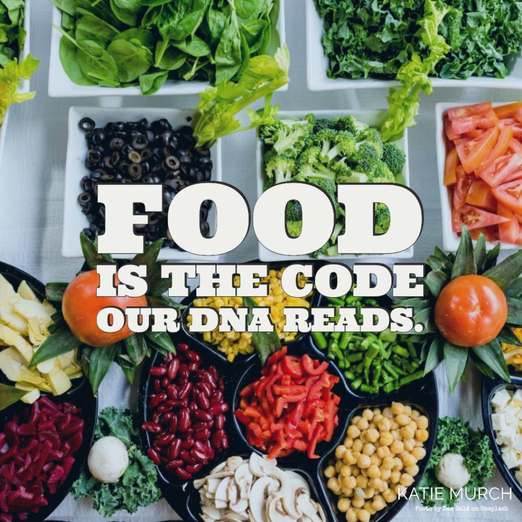 Quote is in front of a table with various square bowls and serving platters of raw vegetables like broccoli, spinach, kale, olives, tomatoes, chickpeas, bell peppers, corn, beet, mushrooms. Katie Murch and photo credit is on the bottom right of the image.
