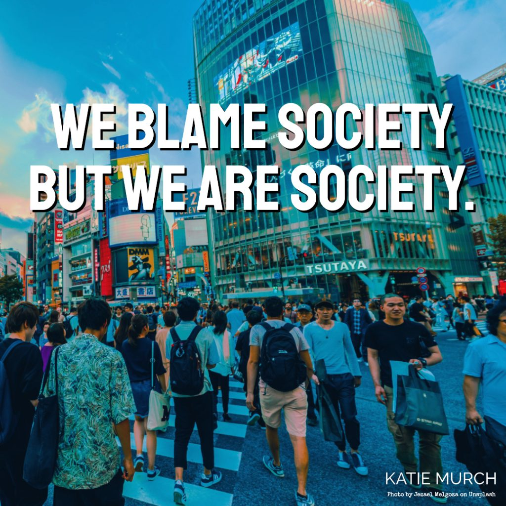 Quote is in front of a busy downtown crosswalk in an Asian town. Tall buildings and advertisements are seen in the back while people holding shopping bags, totes, and backpacks are walking towards and away from the viewer. Katie Murch and photo credit is on the bottom right of the image.