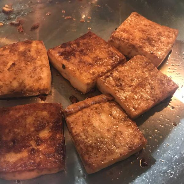 Golden brown square pieces of tofu is on top of a stainless steel pan.