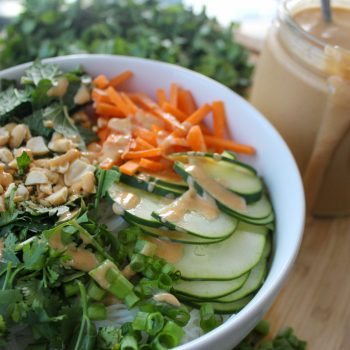 A white bowl holding white noodles is topped with sliced cucumber, julienned carrots, crushed peanuts, chopped cilantro, mint, and scallions. Next to it is a jar with brown sauce and a pile of greens.