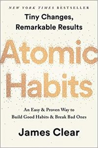 """Book is light yellow-white with """"Atomic Habits"""" in gold and """"New York Times Bestseller,"""" """"Tiny Changes, Remarkable Results,"""" """"An Easy & Proven Way to Build Good Habits & Break Bad Ones,"""" and """"James Clear"""" in black. All text are centered."""