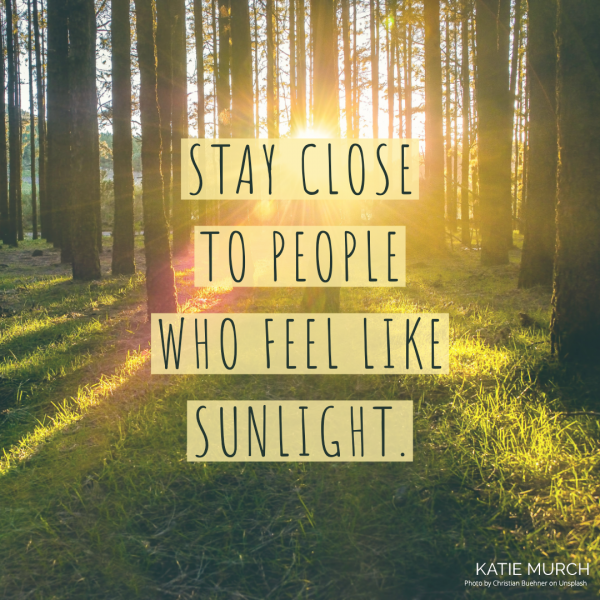 Quote is in the middle and in black font and a yellow highlight background. The image behind the quote is of a forest with sunlight filtering between tall trees. Katie Murch and photo credit is on the bottom right of the image.