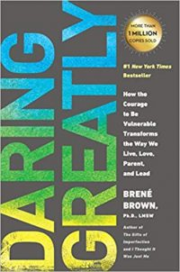 """Book cover is grey with """"Daring Greatly"""" in a yellow-blue-green ombre effect. A gold emnlem highlights, """"More than 1 million sold"""" above the name of the author """"Brene Brown, Ph.D LSNW""""."""