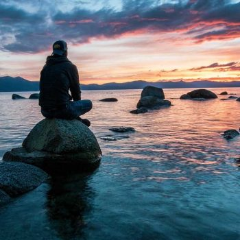 A masculine figure is sitting on a boulder surrounded by semi-calm water. In the distance is the silhouette of mountains lit by the sunset behind it.